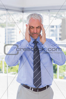 Stressed businessman rubbing his temples with eyes closed