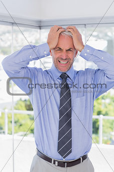 Stressed businessman with hands on his head
