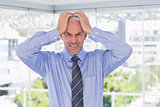 Frustrated businessman with hands on his head
