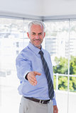 Smiling businessman extending arm for handshake