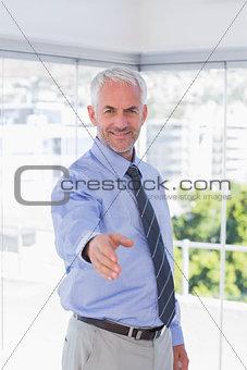 Smiling businessman extending arm for handshake