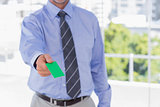 Businessman offering green business card