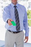 Businessman giving green business card