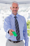 Happy businessman giving green business card