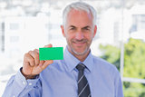 Happy businessman showing green business card