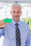 Smiling businessman showing green business card