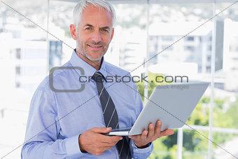 Smiling businessman holding laptop