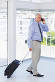 Businessman pulling suitcase and talking on phone