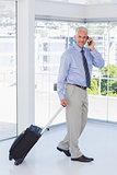 Businessman pulling suitcase and talking on phone smiling at camera
