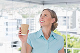 Businesswoman holding disposable coffee cup and looking up
