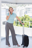 Smiling businesswoman on the phone with suitcase