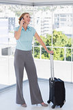 Smiling businesswoman on the phone leaning on suitcase