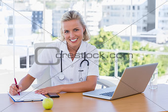 Beautiful nurse writing on a notepad on her desk