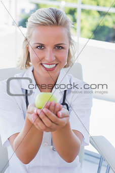 Blonde nurse holding a green apple