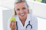 Smiling blonde nurse holding a green apple