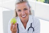 Smiling blonde nurse holding a green apple