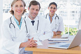 Happy doctors posing at their desk