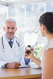 Patient holding a bottle of pills in front of doctor