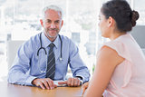 Attractive doctor sitting in front of patient