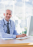 Smiling doctor typing on his computer