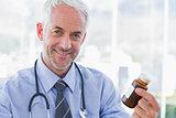 Smiling doctor holding medicine jar
