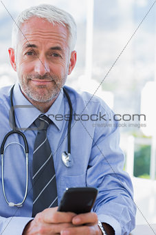 Attractive doctor using his smartphone