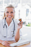 Smiling nurse holding a medicine jar