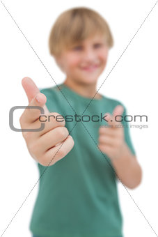 Blonde boy giving thumbs up and pointing