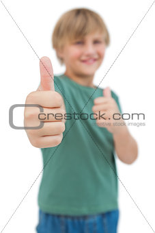 Blonde boy giving thumbs up focus shot