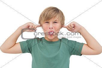 Blonde boy blocking his ears with fingers