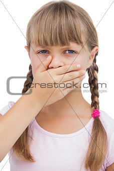 Little blond girl with her hand on her mouth