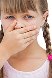 Portrait of a little blond girl with her hand on her mouth
