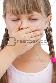 Little blond girl with her hand on her mouth with her eyes closed