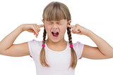 Funny little girl clogging her ears and wincing