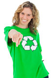 Smiling environmental activist wearing green shirt with recycling symbol on it and pointing the came