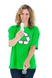 Environmental activist holding energy saving light bulb and a light bulb