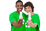 Cheerful activists holding energy saving light bulbs