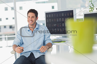 Cheerful photo editor in his swivel chair