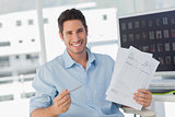 Cheerful photo editor pointing at documents