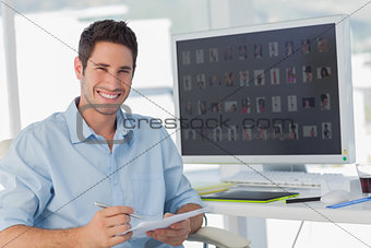 Handsome photo editor holding documents