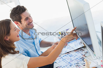 Photo editors pointing at a computer screen