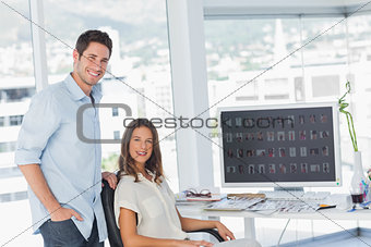 Two photo editors posing in their office