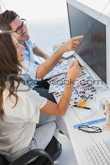 Attractive photo editors pointing at computer
