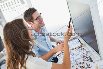 Cheerful photo editors working on computer
