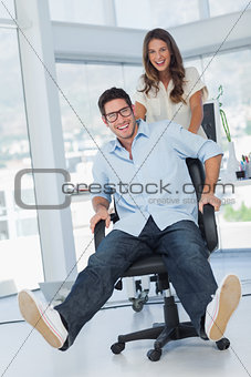 Happy designers having fun with a swivel chair