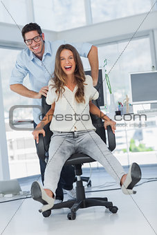 Cheerful designers having fun with a swivel chair