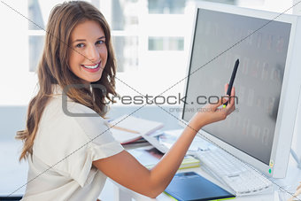 Attractive photo editor pointing at the screen