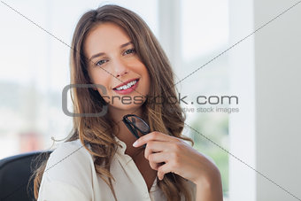 Businesswoman posing while she is holding her reading glasses