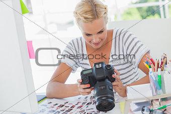 Blonde photo editor looking at a digital camera