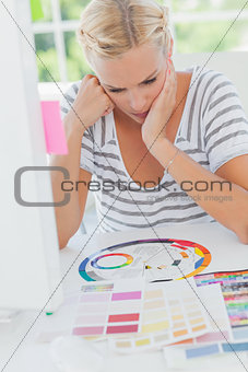 Thoughtful interior designer looking at a colour wheel